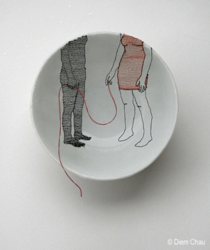 Still life photo of a porcelain bowl seen from above with an illustration of two people holding a red thread.