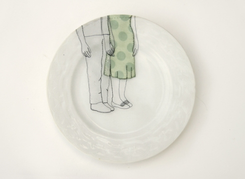 Still life photo of a porcelain plate seen from above with an illustration of a man and a woman holding hands.