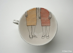 Still life photo of a porcelain cup seen from above with an illustration of two women legs.
