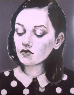 Portrait of a young girl looking down wearing a dotted shirt.