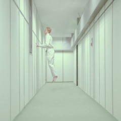 Portrait photo of a young man floating in the air inside an empty white room.