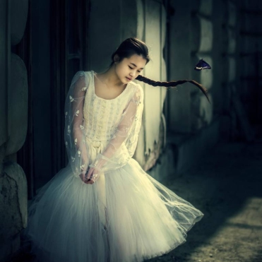 portrait photo of a young woman with a white tulle dress.