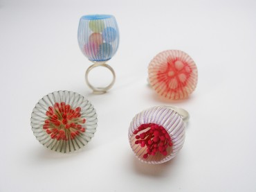 Still life photo of a group of four rings realised with semi transparent and translucent textiles, the shape reminds natural and organic forms taken from nature.