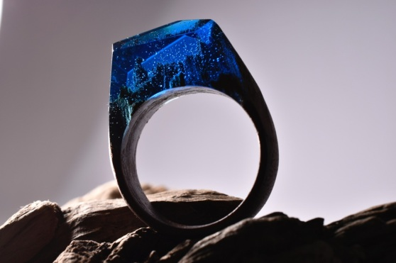 Still life photo of a ring with a blue tiny landscape in it.