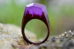 Still life photo of a ring with a tiny purple surreal landscape inside.