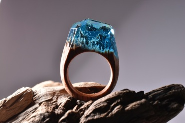 Still life photo of a ring with a tiny blue landscape inside.
