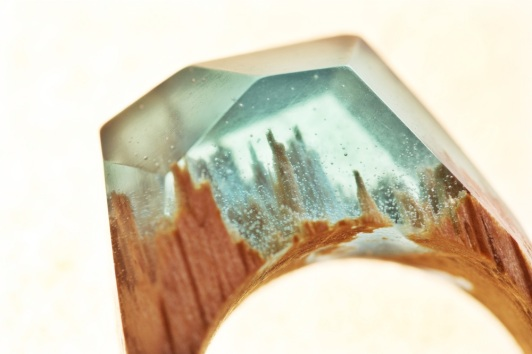 Closeup still life photo of a ring with a tiny aquamarine landscape inside.
