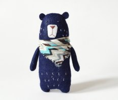 Still life of a Felt Blue Bear With Scarf surrounded by a shite background.