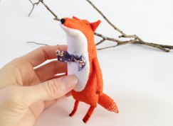 Still life photo of a Felt Fox Toy with a bow handled by a hand on the left of the picture.