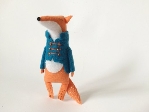 Still life of a Felt Fox With A Military Jacket surrounded by a white background.