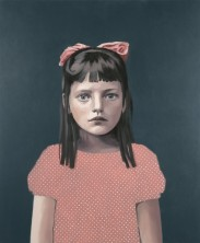 Portrait of a young girl with a pink dress with white dots, a pink bow in her hair and a dark grey background.