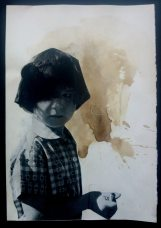 Collage on paper of a baby girl half body decorated with black acrylics and coffee.