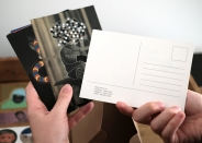 Detail photo of hands that are holding postcards.