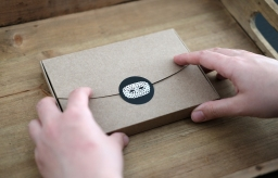 Still life photo of a brown paper box with hands holding it.