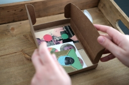Photo of a close up of hands that are opening a brown paper box with art prints inside.