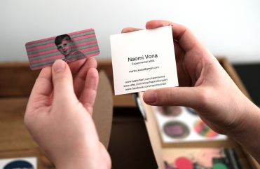 Detail photo of hands that are holding two business cards.