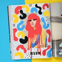 Still life photo of an open fashion magazine with a model photo decorated with colorful pens.