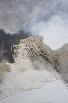 Abstract paintings of fluid golden lines over a black and white background.