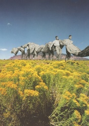 Collage of a group of giant men walking and bringing with them a long textile. The group is walking on a mountain landscape.