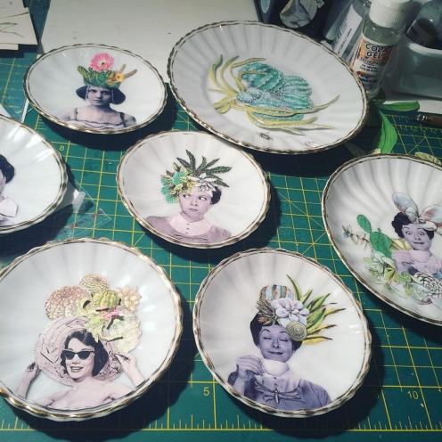 Still life photo from above of a series of porcelain plates with a paper vintage style collage decoration.