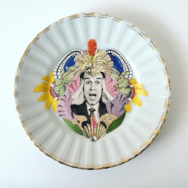 Still life photo from above of a porcelain plate with a paper vintage style collage decoration.