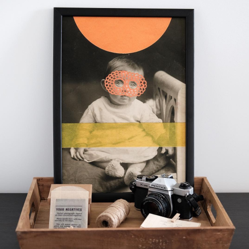 Still life photo of a framed art print with some vintage objects aside.