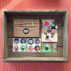 Still life photo of an art gift box, postcards, business cards and stickers seen from above.