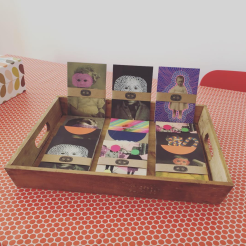 Still life photo of postcards inside a wooden tray.