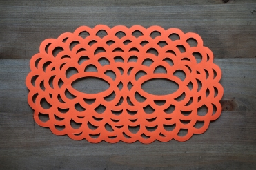 Still life photo of a neon red paper mask seen from above.