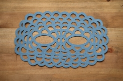 Still life photo of a pastel grey/blue paper mask seen from above.