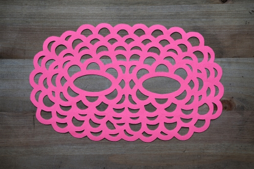Still life photo of a neon pink paper mask seen from above.