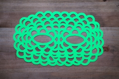 Still life photo of a neon green paper mask seen from above.