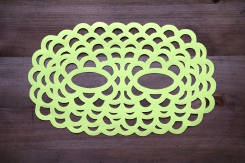 Still life photo of a neon yellow paper mask seen from above.