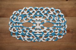 Still life photo of a white and blue paper mask seen from above.