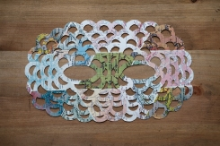 Still life photo of a map pattern paper mask seen from above.