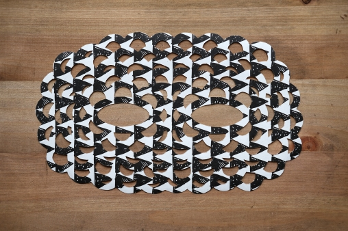 Still life photo of a black and white paper mask seen from above.