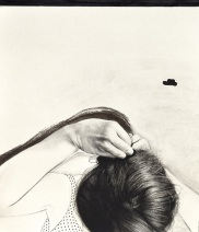 Close up of a woman that is touching her head from above.