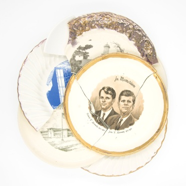 Frontal still life photo of a collage of broken commemorative plates.