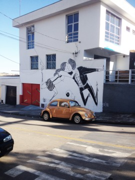 Photo of a white building decorated with a giant murales of a couple kissing.