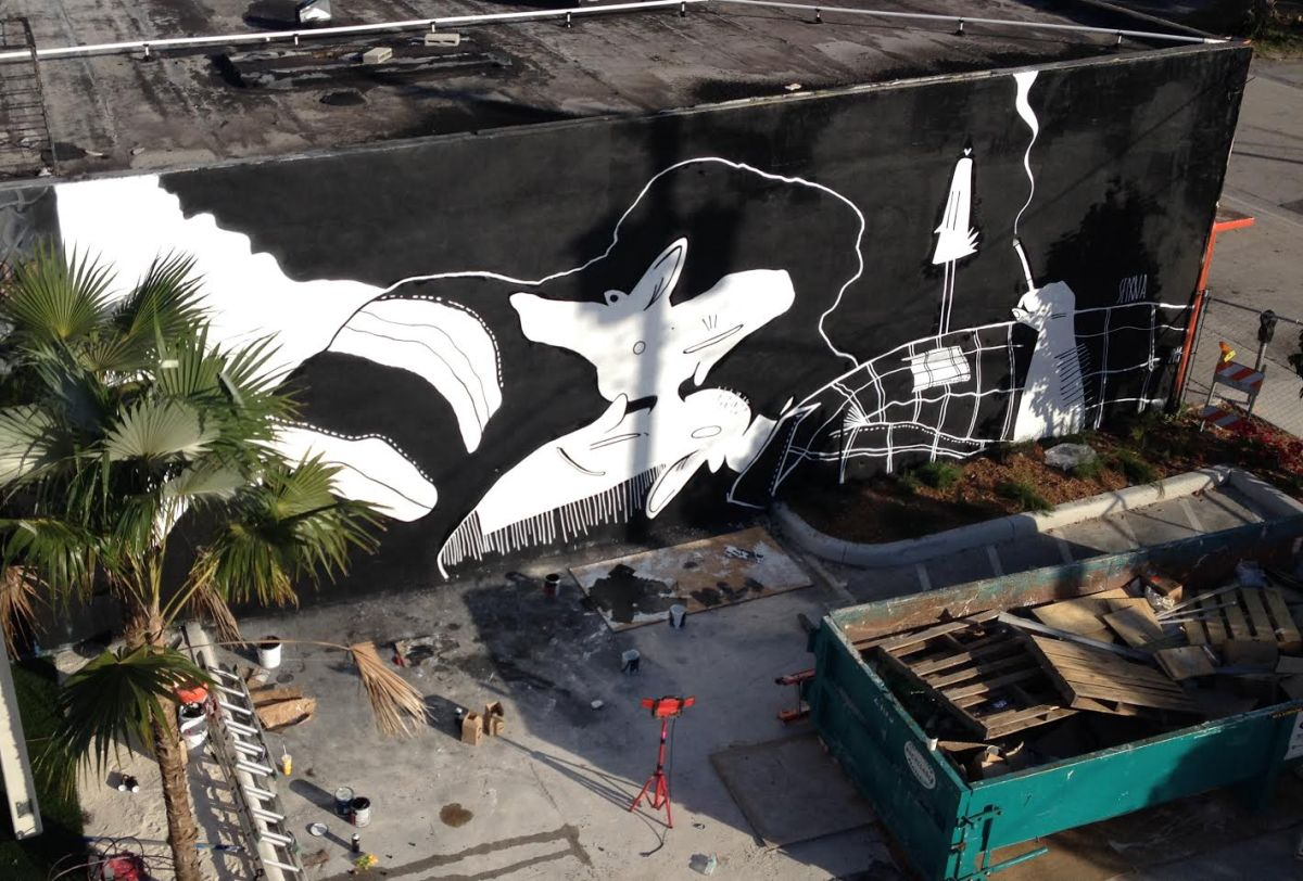 Photo of an aerial view of a giant building with a wall decorated with an illustration of two people kissing