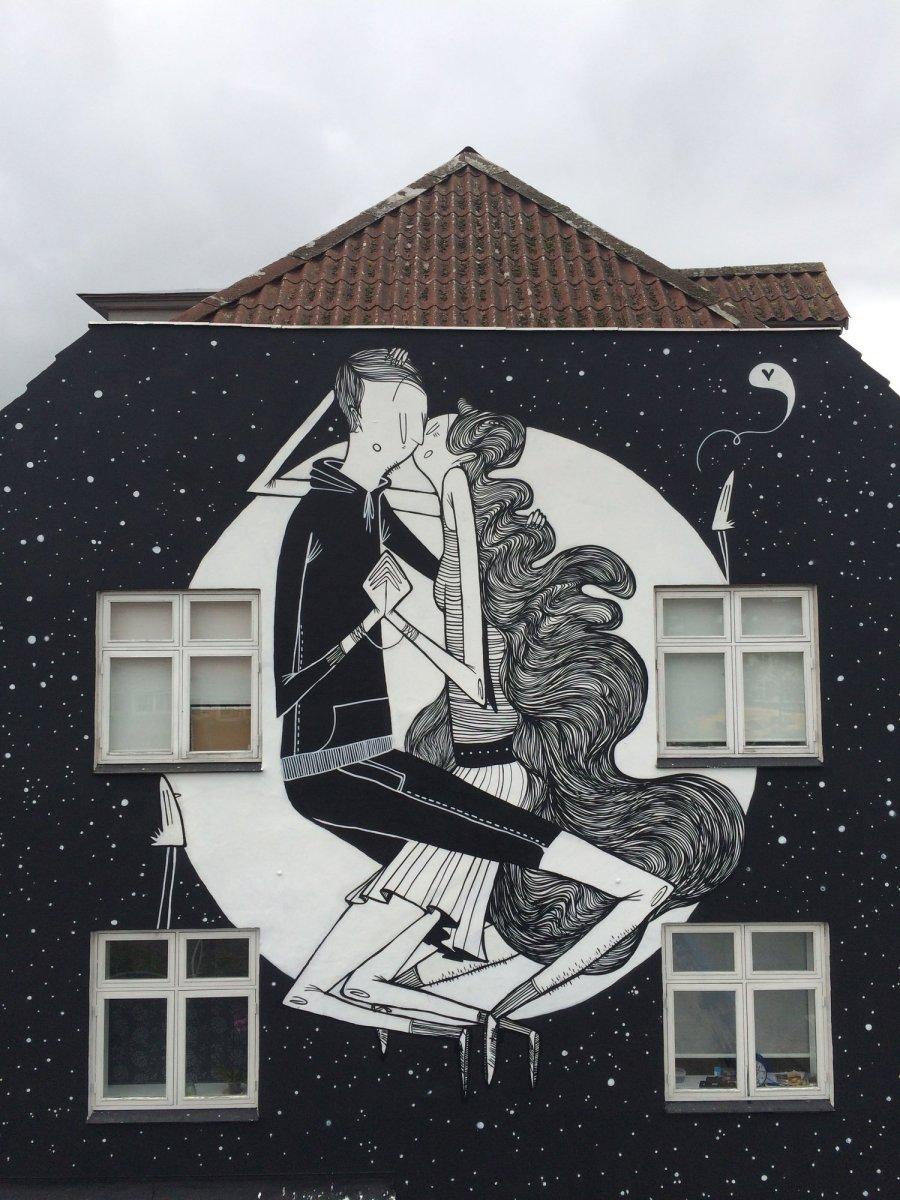 Photo of a wall of a building decorated with an illustration of a couple kissing.