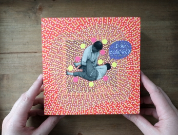 Frontal view, still life photo of a collage on wood panel with hands.