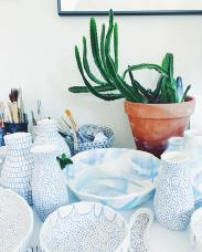 Still life photo of a plant and dinnerware.