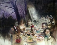 Group of people sit around a table, eating outside in the woods.