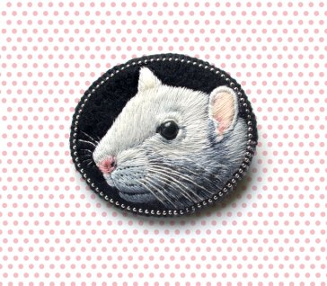 Still life of a mouse brooch.