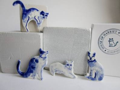Still life of a group of porcelain brooches cat shaped.