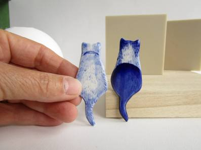 Still life of a couple of porcelain brooches cat shaped.