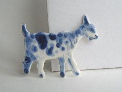 Still life of a porcelain goat shaped brooch.