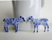 Still life of a couple of porcelain lamb shaped brooches.