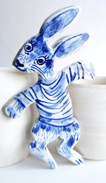 Still life of a porcelain rabbit shaped nursery wall hanging.